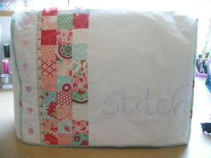Sewing machine cover with patchwork and piping.