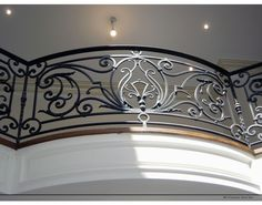 A custom handmade forged iron railing that defines an entry with gorgeous scrolls, curves and a crest.