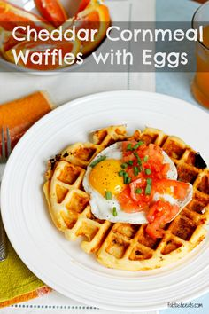 Savory cornmeal waffles, loaded with cheddar and chicken sausage, topped with fresh tomatoes and a yolk-y egg, are sure to please and make your mouth water!