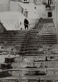 Pepi Merisio, Grandma splitting Wood on the Stairs, Italy, 1952