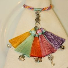 Unusual napkin rings with pastel coloured tassels and little charms dangling fro