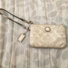 Coach Wristlet Authentic. Good condition, white color is dirty from use. Noticeable wear from use on the outside & satin finish inside. Coach Accessories