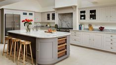 A bespoke Harvey Jones Shaker kitchen design featuring our curved cabinets and an island with storage baskets DORIS - LOOK AT THE BACKSPLASH