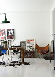 Nowoczesne wnętrze: biel na ścianach i podłodze przełamana za pomocą oryginalnych grafik oraz brązowych mebli.