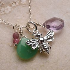 """A silver bee pendant hangs with a mix of colorful gemstones to create this lovely necklace. The bee is surrounded by purple amethyst, green chrysoprase and pink tourmaline and hangs from a sterling silver chain at the length of your choice. Amethyst is said to be the """"dream stone"""" and promotes spiritual wisdom. Amethyst is the birthstone for february. Amethyst is connected with the 7th chakra (crown) which promotes enlightenment, cosmic consciousness, energy, perfection. Chrysoprase is said…"""