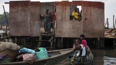 Residents of Makoko look on at damaged dwellings