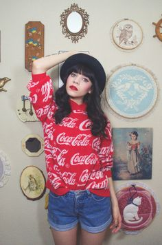 Pin up makeup and hair. Lovely old-school outfit with a coca cola sweater,black hat and shorts