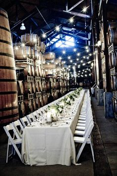 WOW! This table setting is breathtaking. We can't get over the wine barrels and the lights! {Firestone Vineyard}