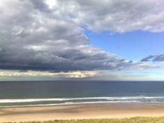 View from Bamburgh castle, rain sweeps across the horizon forming bands of colour.