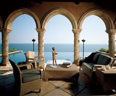 """Cher- Refuge on a Malibu Bluff  Photography by Mary E. Nichols   """"The infinity-edge pool is where I spend all of my time in the summer,"""" says Cher. From the loggia is a view of the pool, which seemingly overflows into the Pacific Ocean. An Egyptian sculpture rests on a woven-reed low table. Standing bronze oil lamps are beneath arches supported by columns with vines carved in relief. http://www.architecturaldigest.com/celebrity-homes/2005/cher-malibu-home-slideshow#slide=1"""
