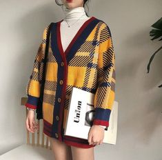 Oversized checkered yellow vest with white turtle neck.