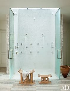 35 Stunning Shower Ideas from the Pages of AD Photos | Architectural Digest [African stools sit in front of the dual-head shower at Ellen DeGeneres and Portia de Rossi's Beverly Hills home. The serene space is set below a skylight and is sheathed in tile by Country Floors.]