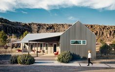 Corrugated metal covers the exterior of this streamlined home, echoing the serene palette of whites and grays that dominates inside the structure.