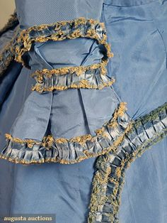 """BLUE SILK FAILLE VISITING DRESS & BONNET, c. 1870   Go Back Lot: 66   April 2009 Vintage Fashion and Textile Auction   New York City   5 pieces, most trimmed w/ box pleated & fringed self fabric: short bodice w/ long sleeves, trained skirt w/ scalloped edge, overskirt & bow back belt w/ fringed trim, woven straw & blue faille spoon bonnet, all pieces lined w/ cream cotton or buckram, B 34"""", W 22"""", Skirt L 39""""-60"""", Overskirt L 12""""-35"""", (scattered spots at underarms, few stains on other…"""