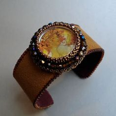 While preparing for my recent art show, I made a lot of new cuffs. These ones are a little different from the others I usually make. These ones have a beaded centerpiece and then the cuff is covered in ultrasuede. Here's one that I made using one of my handmade cabochons with an Alphonse Mucha print