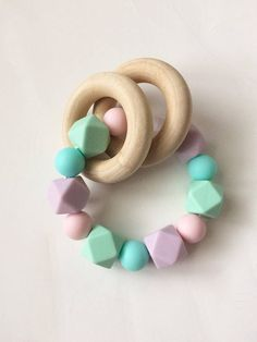 This adorable little Silicone Teething Ring will do just the trick for those not so fun days of teething. Simply allow them to teeth, chew and gnaw on the different shaped silicone beads and untreated, natural wood rings. The full silicone ring and wooden rings allow for easy