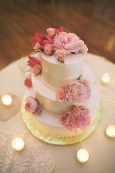 White cake with various shades of pink flowers.     Photography by JLBwedding.com