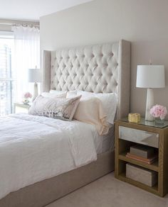 Beige tufted wingback bed dressed in white linen bedding flanked by wood and mirrored nightstands topped with Alabaster Quatrefoil Lamps.
