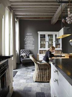 le mur du fond de la cuisine donne la préférence à une peinture couleur taupe pour son aspect confortable et chaleureux. Dans cette palette de couleurs neutres, des rideaux de coton couleur lin habillent les fenêtres qui ouvrent sur le jardin.