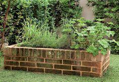 """Canteiro especial    O canteiro de tijolos atende ao pedido da moradora, que queria uma horta no jardim. """"Fazer uma caixa um pouco mais alta, com 40 cm de altura, facilita no manuseio dos temperos"""", explica."""