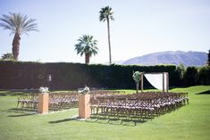 Arrangements Floral + Party Design — Rancho Mirage, Lauren + Chris | Wooden Canopy, Woodend cross back chairs, white rose petals along the aisle, wooden pillars with white and green florals, wedding ceremony, desert wedding