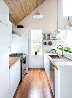 You can opt for an asymmetrical layout, using various approaches. One involves focusing tall cabinets or a bank of appliances on one side of the room, with base and wall units on the other. Or you can go with a mix of tall and wall units along one side, with a single run of base units on the other if, for example, you have an open-plan space