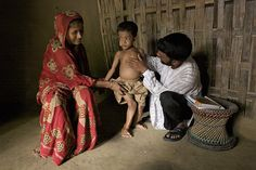 """Tariq (age 7) has rickets – a bone-softening disorder that is caused by chronic malnutrition. It has already killed two of his siblings. """"I was afraid Tariq would die just like my other children,"""" his mother (left) said. I try to follow the advice I receive in nutrition sessions. Tariq has already improved.""""     Pictured: A field health monitor examines Tariq during a home visit, on the island of Moheshkhali, Bangladesh.  ©UNICEF/Shehzad Noorani  www.unicef.org/photography"""