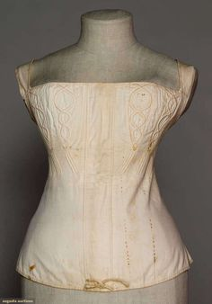"White cotton corset, 1820s. Augusta Auctions: ""White cotton twill, corded designs below bust & on bust inserts, carved bone back-lacing eyelets, muslin lining, B 28"", CFL 15"" Brooklyn Museum"""