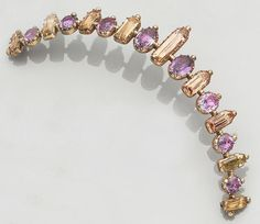 An early 19th century amethyst and topaz tiara, circa 1830,  composed of graduated row of alternate oval-cut amethysts and long rectangular-cut topaz, to closed back settings, tiara length 16.0cm.,