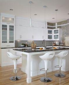 Cuisine contemporaine blanche. Les armoires de cuisine et l'îlot ont été réalisés en polyester de style shaker. Comptoir en granit noir.