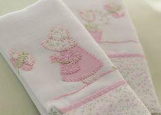 As Fraldas de Ombro são bordadas à mão com desenho da delicada Camponesa e uma flor cor de rosa. Feitas totalmente em algodão, têm barra de tecido estampado com as delicadas flores campestres, tema da coleção. Cada uma mede 68 x 32 cm.