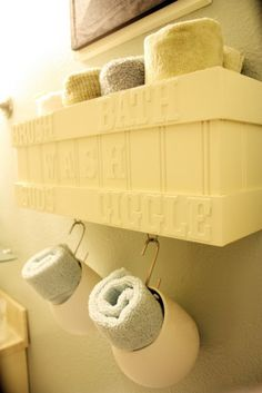 Use old flower pots attached to the wall.  Roll up your towels and store them in the flower pot or troughs.