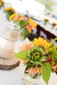 Tables were decorated candle light centerpieces situated on a slabs of native wood decorated with burlap flowers and grapevine's  flanked by floral arrangements in mason jars. Simply beautiful!! ~ California Florals fresh from the farms of California! ~Stone Barn Farms~ Wedding/Event Venue