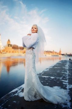 Russian bride in a fur jacket and a lace gown with a train.