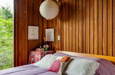 Cores leves, muita madeira e vista para o verde nesse quarto de casal  na Granja Viana.