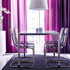 A dining table with white glass top and chrome-plated legs with chairs in lilac with chrome-plated leg frame