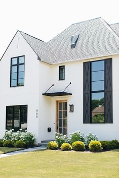 This modern English farmhouse designed by Grand Tradition Homes and Kate Marker Interiors is located in Barrington, Illinois. Farmhouse Landscaping, Modern Farmhouse Exterior, Modern Farmhouse Style, Modern Cottage, Yard Landscaping, Exterior Door Trim, Exterior Paint, Exterior Design, English Farmhouse
