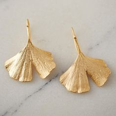 """Hand-cast in a mold created directly from fanned gingko leaves, these elegant earrings were crafted by New York designer Michael Michaud.- Bronze, silver wire- Clean with soap and water as needed- Handmade in the USA1.25""""W, 1.75""""L"""