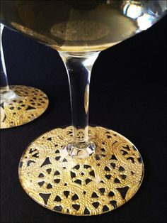 mod podge + doilies + glasses= UPDATE: this was easy and it turned out quite pretty.  I used paper doilies (found in the baking section of hobby lobby) and spray painted them gold.  Then I just cut them up and glued them to the bottom.  Simple and adds a unique touch to plain wine glasses.