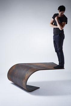 Le designer Paul Cocksedge, est devenu célèbre pour ses installations légères et magiques. Il se fait à nouveau remarquer grâce à sa table basse défiant la gravité. Elle est d'un design épuré et brut, donne l'impression de défier les lois de la gravité, mais grâce à des calculs mathématiques précis, cette table de 450 kg reste stable. La conception en acier laminé est en réalité si solide, que vous pouvez être debout, à l'extrémité, sans que celle-ci ne vacille.