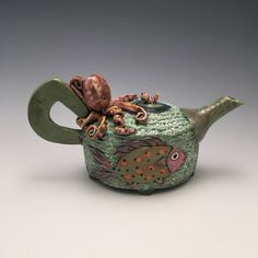 Ocean Friends by Lilia Venier. This beautiful basket is hand built, carved and painted. The octopus on the handle is three dimensional. The teapot has been fired multiple times to about 1800 degrees using colorful and textured glazes which are lead free. It is functional and holds hot water. It is not recommended to be used in the microwave. It is one of a kind piece.