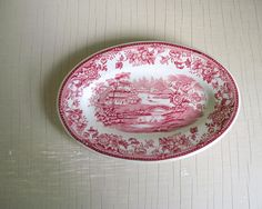 Heres a lovely little oval plate with Clarice Cliffs Tonquin design in red pink transferware. Made by Royal Staffordshire, the dish has a red flowers rim with a country house scene in the center. Great addition to any red tranfersware collection for the table or as wall decor.  • measures 7 x 4 1/2 x 1 • in wonderful vintage condition, little wear, no chips, cracks or crazing  • more vintage table finds: www.etsy.com/shop/gazaboo?section_id=18797675  • enter our shop → gaz...