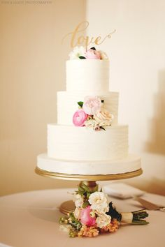 a simple and elegant wedding cake is dressed with pink and white ranunculus, blush peony, blush roses, white scabiosa and white spray roses. a bridesmaid's bouquet rests in front of the cake stand.