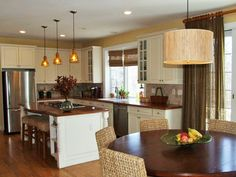 Kitchen with creamy white cabinets and dark wood color counters.