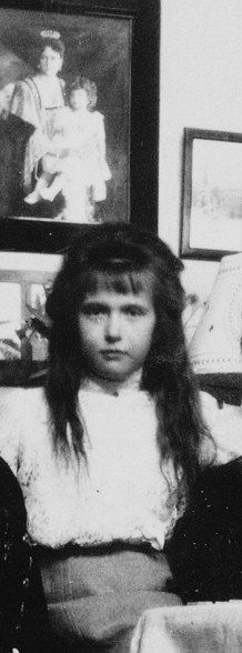 Grand Duchess Anastasia with a picture of her mother and brother behind her