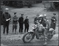 Photo of Steve McQueen drifting the big Triumph on a climb, leg extended for stability ISDT 1964