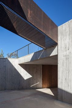 Concrete warehouse and steel bridge. Farm Surroundings by Arnau Estudi d'Arquitectura. Photo by Marc Torra. #architecture #concrete in Architecture