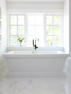 Chic white master bath boasts a gleaming white pedestal tub and a gooseneck tub placed atop a white marble chevron tile floor.