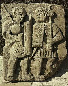 Two Roman soldiers with helmets,dagger and pilum (lance of the Roman infantry). Relief on a Roman column from the praetorium of Mogontiacum (Mainz,Germany) Roemisch-Germanisches Zentralmuseum, Mainz, Germany