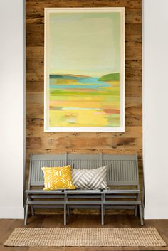 A barnwood accent wall paired with old stadium seating and abstract artwork sets a modern-rustic vibe.